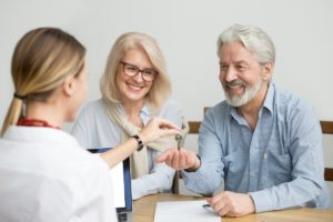 woman giving keys to older couple