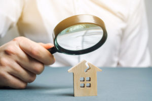 person looking at house through a magnifying glass