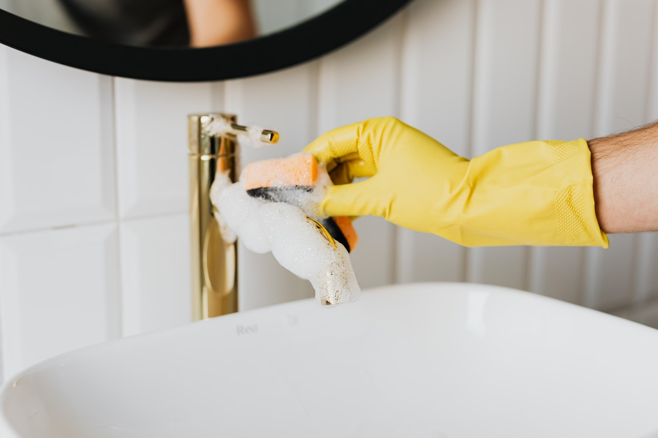 person cleaning a faucet